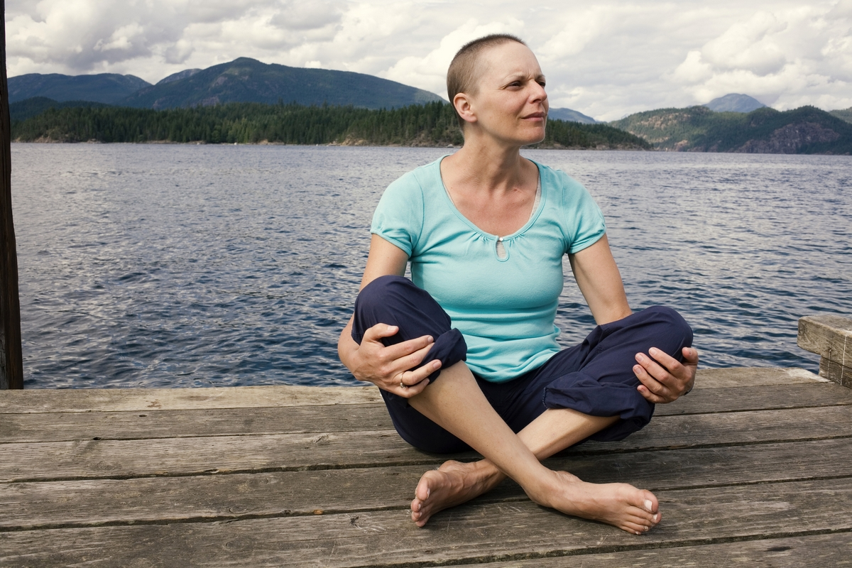 Woman sitting cross legged on a dock.